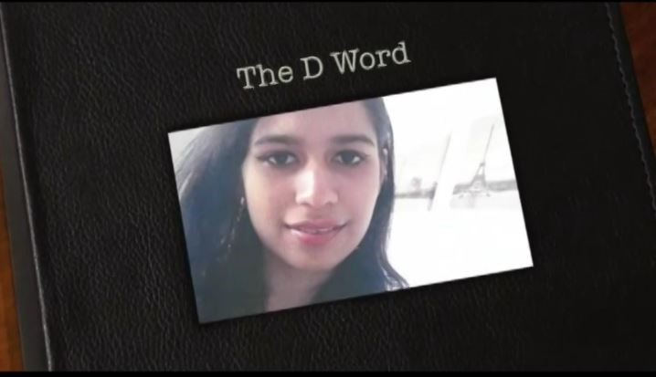 The photo shows Aisha on the front cover of a photo book. The photo book is labelled The D Word.